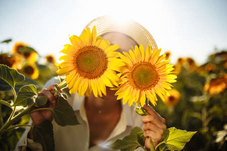 Beauty joyful young woman with sunflowers enjoying nature and laughing on summer sunflower field. Female holding sunflowers. Sunflare, sunbeams, glow sun, freedom and happiness concept. Backlit shot.