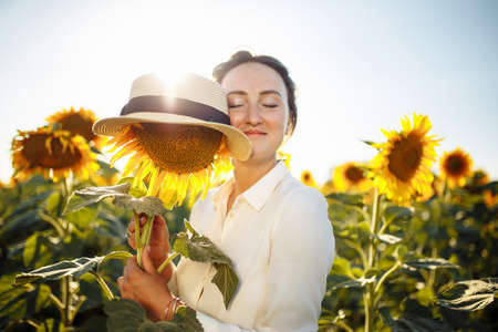 Young woman hugs a single sunflower in a hat on the background of a field of sunflowers on a sunny summer day. Joy, easy, happiness, freedom concept.