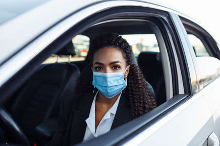 Young woman taxi driver sits in a car behind the steering wheel and driving during the covid-19 quarantine. Business trips during pandemic, new normal and coronavirus travel safety concept