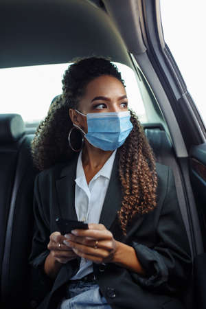 Young business woman in a mask checking her mobile cell phone on a backseat of a taxi during covid-19 quarantine. Business trips during pandemic, new normal and coronavirus travel safety concept