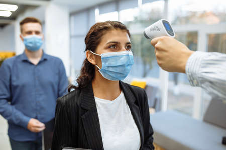 Office workers are checked with a distant non contact thermometer during coronavirus pandemic. Young business woman passing temperature control at the office corridor to prevent covid-19 spread.