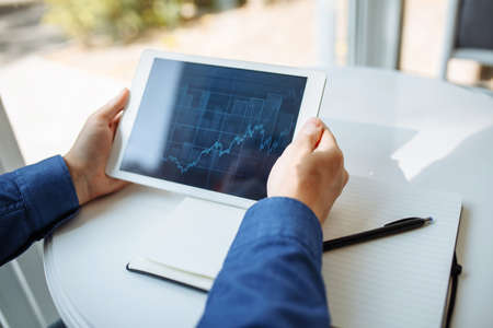 Closeup of a businessman hands with a tablet. Young man sits in a cafe and checking the pictogram graph on a tablet. Working leading business from a distance and remotely. Heath care concept