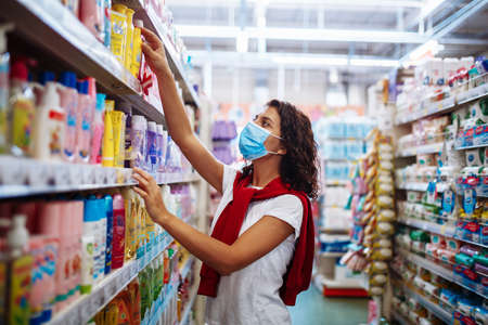 Young woman picks up the disinfecting and cleaning scour at a supermarket wearing a medical sterile mask during the coronavirus pandemic quarantine. Healthcare and home sanitizing concept