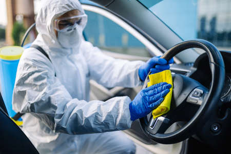 Disinfection professional cleans up a steering wheel of a car with a yellow rug. Sanitary service worker disinfects the vehicle's driver seat place. Covid-19 spread prevention. Health concept