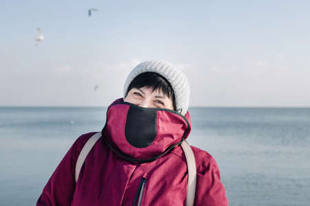 Portrait of a woman wearing magenta red jacket covering from wind and cold during the winter at a seaside beach on a snowy day near the water. Lifestyle, health and walking concept.