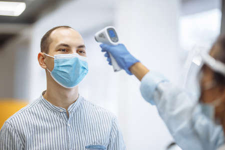 Nurse measures temperature of a patient hospital visitor with a non contact thermometer. People wearing protective medical masks. Coronavirus prevention and healthcare concept