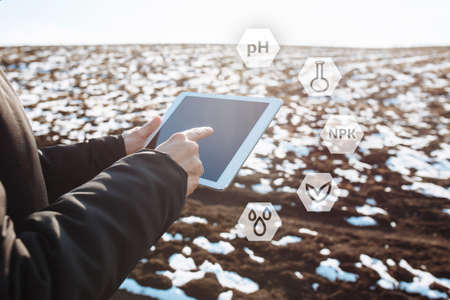 Tablet in the hands of a farmer checking the preparation process and soil readiness for seeding new crop. Farmer in the field, controlling the growth and development of wheat. Reklamní fotografie