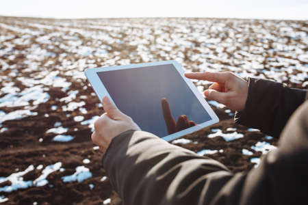 Tablet in the hands of a farmer checking the preparation process and soil readiness for seeding new crop. Farmer in the field, controlling the growth and development of wheat. Agricultural concept Reklamní fotografie
