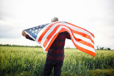 Young man waves an american flag at the green field of wheat. Male celebrates USA independence day on a sunny day. Holidays concept