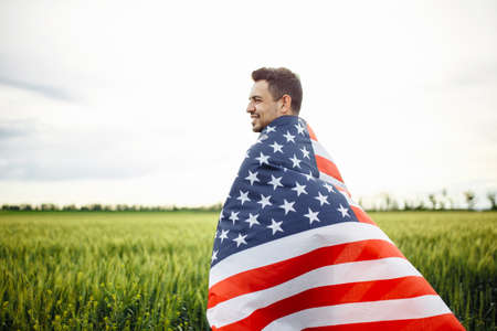 Young man wrapped in the american flag at the green field of wheat. Male celebrates USA independence day on a sunny day. Holidays concept Reklamní fotografie