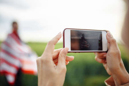 Closeup of a woman taking picture on the mobile smart phone of a man wrapped in american flag. Celebration of USA independence day at a green wheat field. Holidays concept Reklamní fotografie