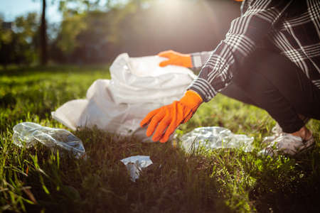 A woman collects and puts used plastic bottle into a trash bag. A volunteer cleans up the park on a sunny bright day. Clearing, pollution, ecology and plastic concept