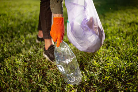 A man volunteer collects a transparent plastic bottle from a green lawn and throws into a trash bag. Volunteer cleans up the park on a sunny bright day. Clearing, pollution, ecology, plastic concept