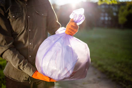 Young man volunteer hold a trash bag in his hands outdoors wearing gloves. A volunteer cleans up the park on a sunny bright day. Clearing, pollution, ecology and plastic concept Reklamní fotografie