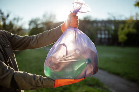 Young man volunteer hold a trash bag in his hands outdoors. A volunteer cleans up the park on a sunny bright day. Clearing, pollution, ecology and plastic concept
