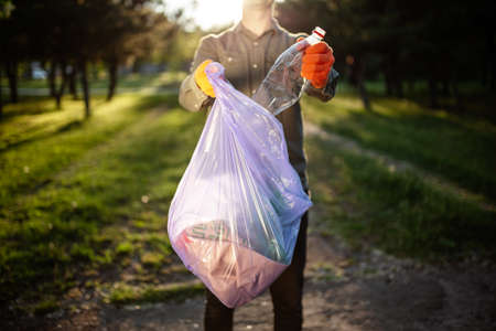 A man worker throws a plasitc bottle into a garbage bag. A volunteer cleans up the park on a sunny bright day. Clearing, pollution, ecology and plastic concept