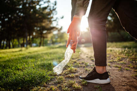Man picks up litter outdoors, collecting used plastic bottle trash. A volunteer cleans up the park on a sunny bright day. Clearing, pollution, ecology and plastic concept