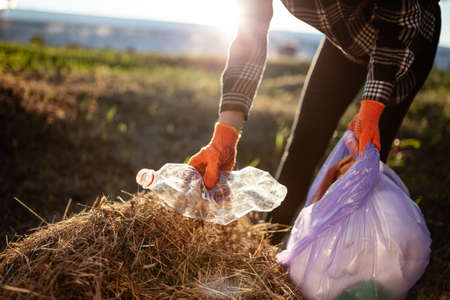Woman wearing gloves collects used plastic bottle and throws it into trash bag. A volunteer cleans up the park on a sunny bright day. Clearing, pollution, ecology and plastic concept