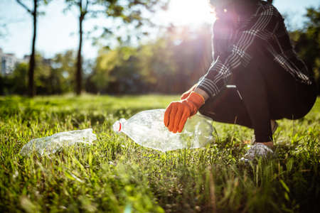 Woman collects used plastic bottle from the green grass lawn. A volunteer cleans up the park on a sunny bright day. Clearing, pollution, ecology and plastic concept Reklamní fotografie