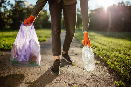 Young man walks with a trash bag and used plastic bottle in his hands wearing gloves. A volunteer cleans up the park on a sunny bright day. Clearing, pollution, ecology and plastic concept