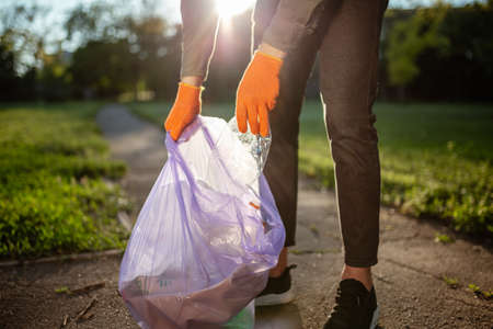 Young man worker throws used plastic bottle into a trash bag. A volunteer cleans up the park on a sunny bright day. Clearing, pollution, ecology and plastic concept