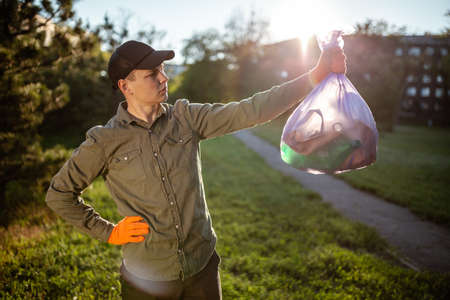 A man worker holds a trash bag in his hand outdoors. A volunteer cleans up the park on a sunny bright day. Clearing, pollution, ecology and plastic concept