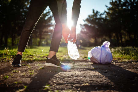 A man collects garbage from the ground to clean environment. A volunteer cleans up the park on a sunny bright day. Clearing, pollution, ecology and plastic concept
