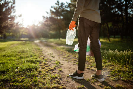 Young man walks with trahs bag and used plastic bottle in his hands. A volunteer cleans up the park on a sunny bright day. Clearing, pollution, ecology and plastic concept