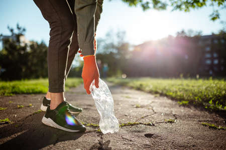 Young man volunteer collects used plastic bottle from the ground outdoors wearing gloves. Volunteer cleans up the park on a sunny bright day. Clearing, pollution, ecology, plastic concept