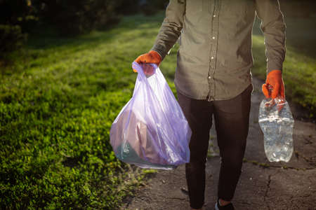 A young man walks with a trash bag and used a plastic bottle in his hands wearing gloves. Reklamní fotografie