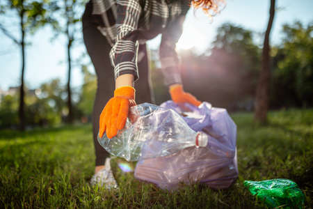 A woman collects and puts used plastic bottle into a trash bag.