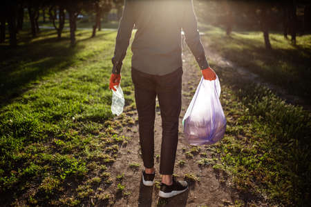 Young man walks with trahs bag and used plastic bottle in his hands. Reklamní fotografie