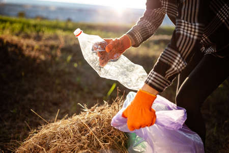Woman wearing gloves collects used plastic bottle and throws it into trash bag.
