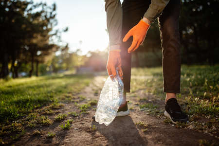 Man picks up litter outdoors, collecting used plastic bottle trash.