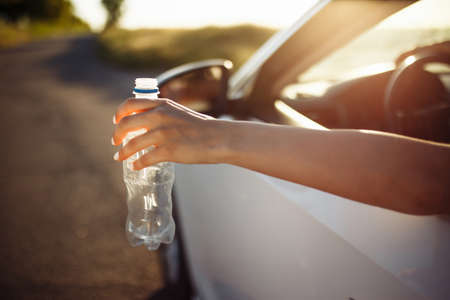 Woman's hand throwing a plastic bottle out of the car's window. Driver throws used water bottle on the road. Irresponsible pollution of environment and garbage concept