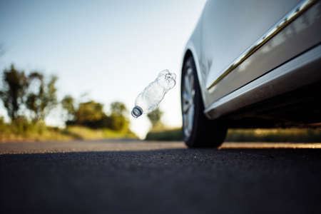 Used plastic bottle falling down on the road from the car's window. Pollution of the environment by ecologically irresponsible people. Waste and garbage on the roads concept Reklamní fotografie
