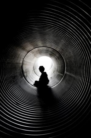 tunel: La silueta del niño que estaba sentado con la luz al final del túnel Foto de archivo