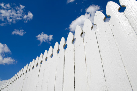 White fence and blue sky with clouds
