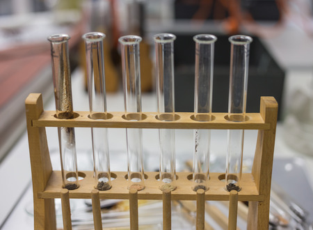 Various test tubes in wooden stand