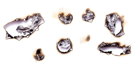 Collection of burnt holes in a piece of paper isolated on white background photo