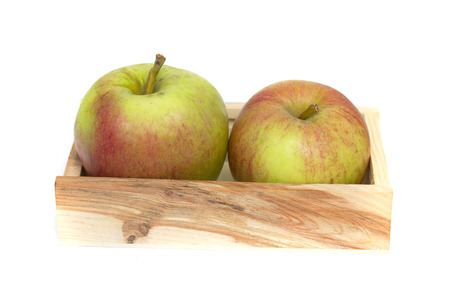 green apples in a wooden crate isolated on white photo