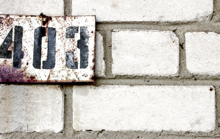 number plate on brick wall photo