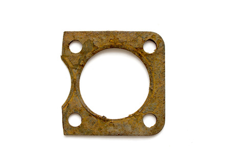 concision: Part of the old rusty cylinder head gasket isolated on white background