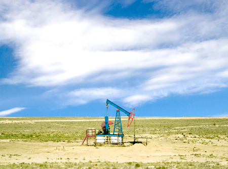 pumping oil from an oil well on the background of sky with clouds photo