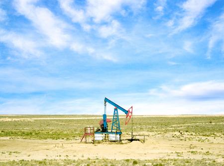 torres petroleras: bombeo de petr�leo de un pozo de petr�leo en el fondo de cielo con nubes