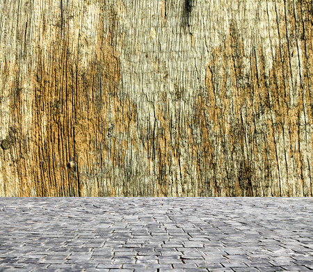 uncommon: wooden fence rough background and vintage stone pavement foreground Stock Photo