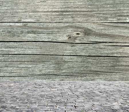 the workpiece: wooden fence rough and vintage stone pavement foreground