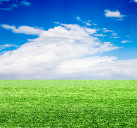 Green field under blue clouds sky. photo