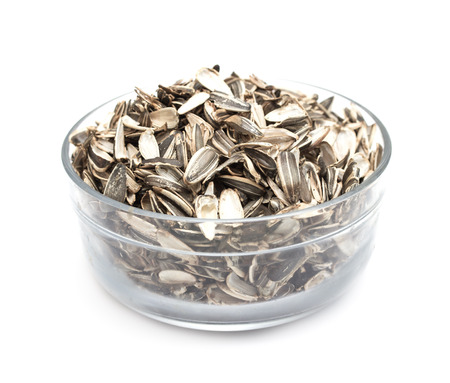 sunflower seeds in a glass bowl on a white background