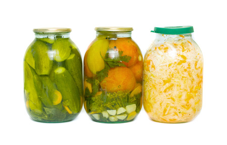 Pickled cucumbers, salted cabbage and tomatoes canned in glass jar on a white background photo